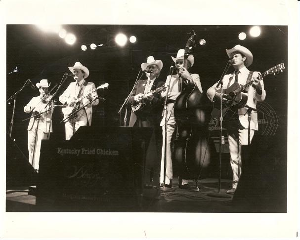 PROFESSIONAL PHOTOGRAPH OF BILL MONROE AND HIS BLUEGRASS BOYS:; 8x10 glossy photo of the group playing onstage. Bill Monroe.
