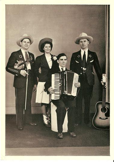 LARGE REAL-PHOTO POSTCARD, SHOWING DOC WILLIAMS, HIS WIFE CHICKIE, BROTHER CY, AND MARION MARTIN:; On-stage in western garb, with their guitar, fiddle and accordion. Doc Williams.