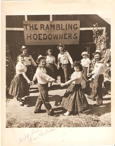 SIGNED, PROFESSIONAL PHOTOGRAPH OF FOUR COUPLES SQUARE-DANCING OUTSIDE A BARN:; Signed by all eight dancers. The Rambling Hoedowners.