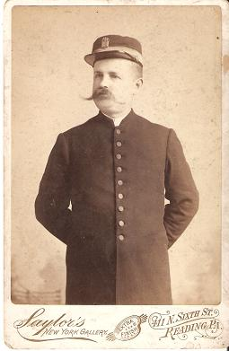 CABINET CARD PHOTO OF CONDUCTOR IN UNIFORM AND HAT WITH BRAID AND COMPANY BADGE:; Charles A. Saylor, Photographer. Reading Railroad.