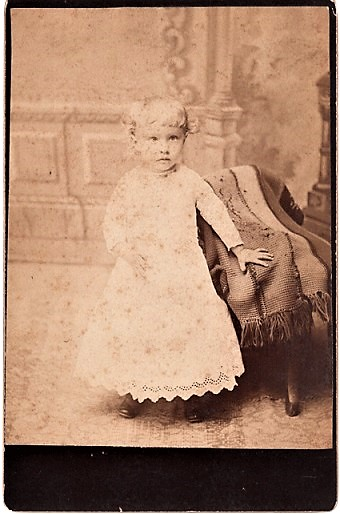 BLUFFTON, OHIO PHOTOGRAPHER'S 1887 CABINET CARD OF A VERY YOUNG GIRL IN VICTORIAN LACE DRESS, LEFT HAND RESTING ON AN AFGHAN-COVERED CHAIR. Bluffton / Triplett Ohio, Will A.