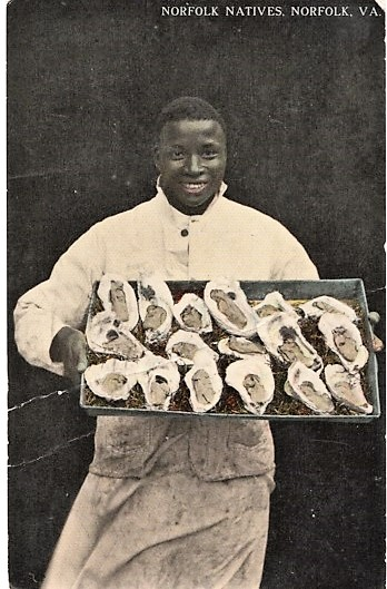 """NORFOLK NATIVES"": TINTED, REAL-PHOTO POSTCARD OF AN AFRICAN-AMERICAN CHEF DISPLAYING A LARGE TRAY OF OYSTERS ON THE HALF-SHELL. Norfolk Virginia."