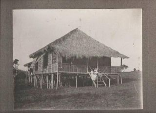 VINTAGE PHOTOGRAPH OF A PHILIPPINO SOLDIER IN UNIFORM (SPANISH-AMERICAN WAR), POSED WITH A WOMAN AND A CHILD ON THE STEPS OF A NIPA HUT. Philippine Islands.