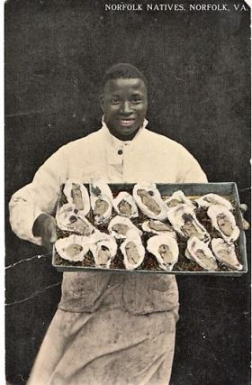 """NORFOLK NATIVES"": TINTED, REAL-PHOTO POSTCARD OF AN AFRICAN-AMERICAN CHEF DISPLAYING A LARGE..."